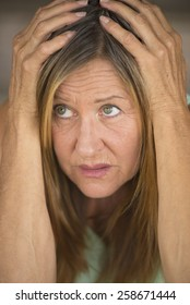 Portrait attractive mature woman, stressed, anxious, scared, unhappy frightened upward look, hands covering head, blurred background.