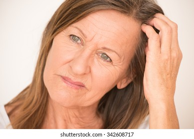 Portrait attractive mature woman with worried facial expression thinking, isolated, bright background.