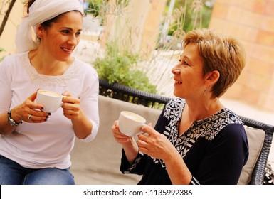 Portrait attractive mature women sitting in summer cafe