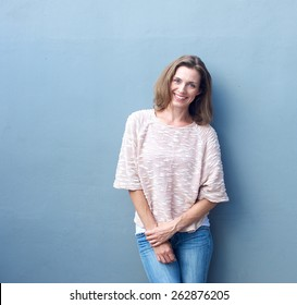 Portrait of an attractive mid adult woman smiling on gray background