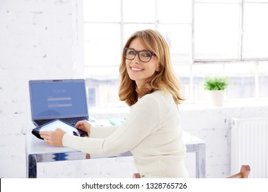 Portrait of attractive middle aged businesswoman sitting at office desk and using her digital tablet while looking back and laughing.