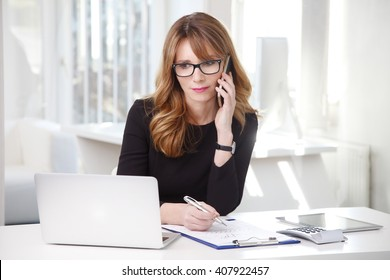 Portrait of attractive middle aged businesswoman sitting in front of laptop and making call while working on new on new project.
