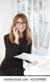 Portrait of attractive middle aged professional woman making call while sitting at office in front of laptop and working on business plan.