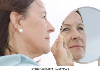 Porträt einer attraktiven Frau mittleren Alters, die in einen Spiegel schaut, mit Fokus auf das Spiegelbild.