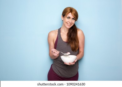 Portrait of attractive middle aged woman with muscular and fit body eating healthy breakfast