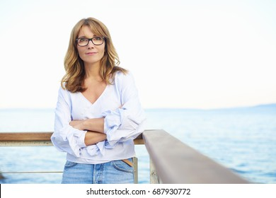 Portrait of an attractive middle aged woman standing outdoor in the background with the sea.