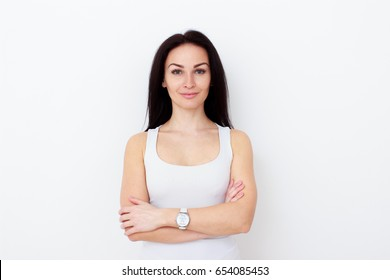 Portrait of attractive middle-aged woman with crossed hands on white wall background