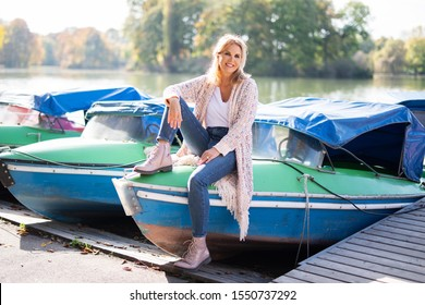 Portrait of an attractive middle-aged woman in front of boats at a lake