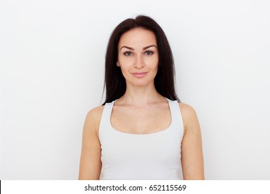 Portrait of attractive middle-aged woman on white wall background