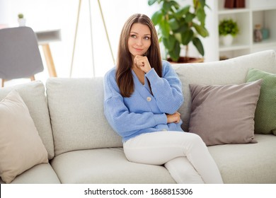 Portrait of attractive minded cheery girl sitting on divan thinking in light flat house apartment indoor