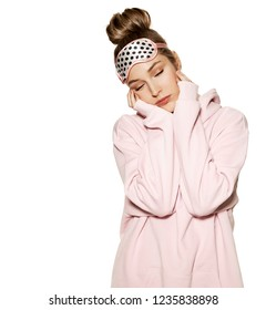 Portrait of attractive model standing in pink sweatshirt and sleeping face mask. Beauty and bedtime concept. Sweet young female falling asleep on white background