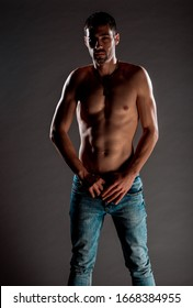 Portrait of an attractive muscular man dressed in blue denim pants