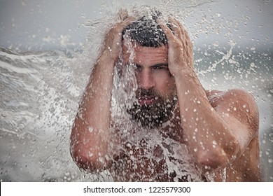 Portrait of an attractive naked bearded man in water. Gran Canaria. Island. Ocean. Hipster guy. The guy in the spray of ocean water.