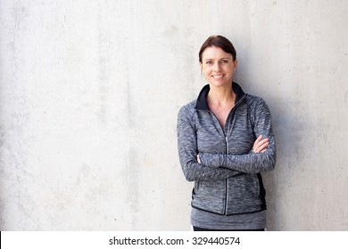 Portrait of an attractive older sports woman smiling against white wall
