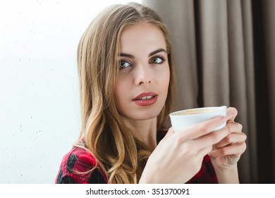 Portrait of attractive peaceful young female with long hair drinking coffee at home