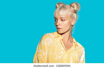 Portrait of attractive pensive young woman looking away. Pretty girl in modern clothes posing inside. Beauty and fashion concept. Copy space in right side. Isolated on blue background