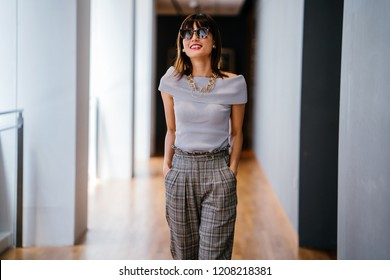 Portrait of an attractive and photogenic middle-aged woman smiling as she walks down a corridor. She is wearing a stylish outfit and sunglasses; she is smiling as she walks.
