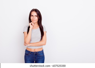 Portrait of attractive playful pensive brunette lady. She is wearing casual outfit and stands on pure white background