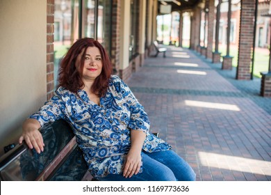 Portrait of attractive plus size mature woman in casual style walk at city at good sunny autumn day and thinking about something. Life of women after 40 years
