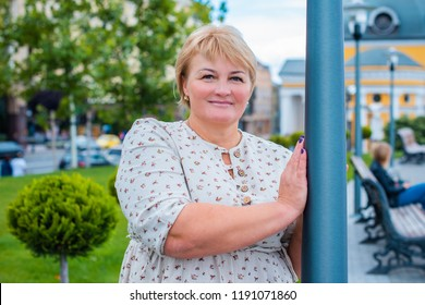 Portrait of attractive plus size mature woman in casual style walk at city at good sunny autumn day and thinking about something. Life of women after 40-50 years