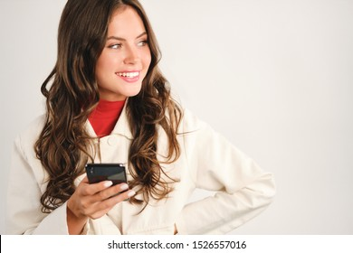 Portrait of attractive positive casual girl with cellphone happily looking aside isolated