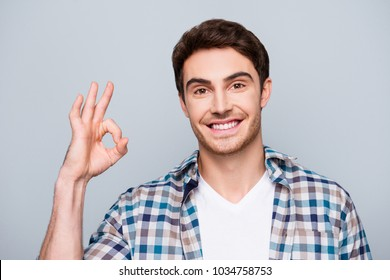 Portrait of attractive, positive guy with stubble in checkered shirt gesturing ok sign with fingers isolated on grey background looking at camera