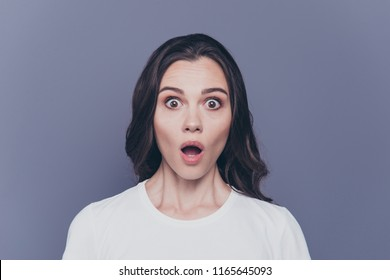 Portrait of attractive pretty charming stylish scared brunette curly-haired girl in casual white t-shirt with staring big eyes and opened mouth, isolated over grey background