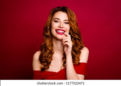 Portrait of attractive, pretty, dreamy, charming, success curly ginger woman look at camera isolated on deep red background holds a finger near the lips and smile