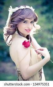 portrait of attractive pricess  outdoors witha rose