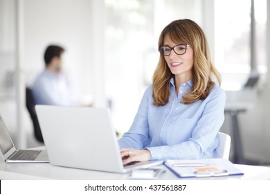 Portrait of attractive professional woman using laptop while working on new project in office.