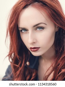 Portrait of attractive red haired young woman with blue eyes.