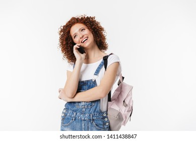 Portrait of attractive redhead curly woman 20s wearing denim jumpsuit and backpack smiling while talking on cellphone isolated over white background