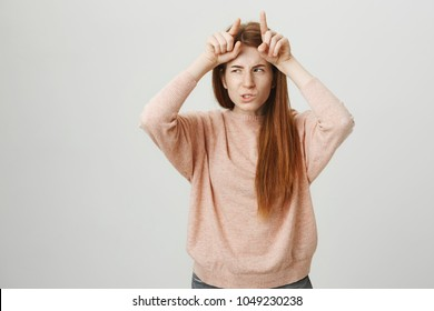 Portrait of attractive redhead european student holding index fingers on forehead like devil horns with evil expression, standing over gray background. Rumor has it that ginger girls have no soul