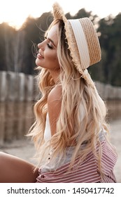 Portrait of an attractive, romantic and c adorable provincial girl with long loose hair in a straw hat. Sunset, soft sunny colors. Nature landscape. Countryside at the background. Summer, summertime
