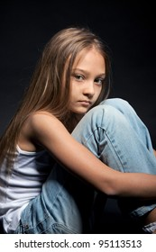 portrait of attractive sad, unhappy, serious calm teenage girl, over black background, concept of child problem, stress, depression
