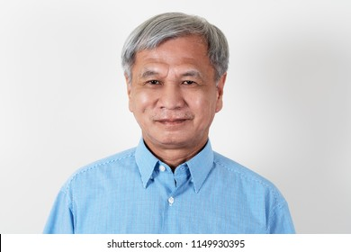 Portrait of attractive senior asian man smiling and looking at camera in studio with white isolated background feeling positive grandpa. Headshot of mature older chinese man or father concept.