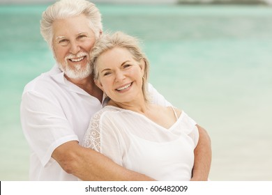 Portrait of attractive senior Caucasian couple in white casual clothes on a tropical vacation beach