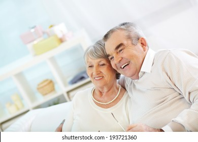 Portrait of an attractive senior couple watching TV