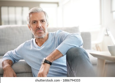 Portrait of attractive senior man with blue sweater relaxing at home
