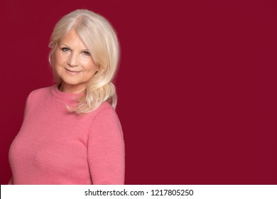 Portrait of attractive senior woman with long grey hair posing on colorful studio background, looking at camera.