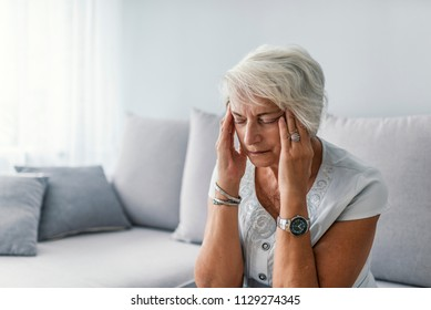Portrait of an attractive senior woman sitting on a sofa at home with a headache, feeling pain and with an expression of being unwell.