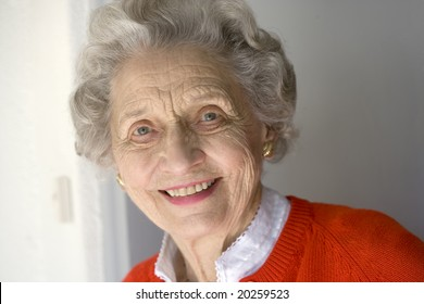 Portrait of attractive senior woman standing by front door