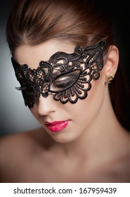 Portrait of attractive sensual young woman with mask. Young attractive brunette lady posing on grey background in studio. Portrait of the beautiful fashion sexy woman with red lips and mask indoor