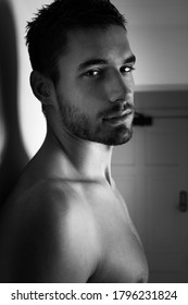 Portrait of attractive shirtless man looking at camera against white wall.