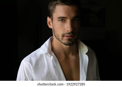 Portrait of attractive shirtless man with stubble standing next to window with open shirt