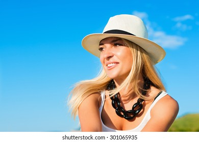 portrait of the attractive, slender, beautiful young Caucasian  blonde girl in a stinny hat. Smiling girl enjoys fine warm sunner weather highly in mountains