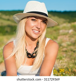 portrait of the attractive, slender, beautiful young Caucasian  blonde girl. Smiling girl enjoys fine warm sunner weather highly in mountains against the sea