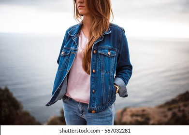 portrait of the attractive, slender, beautiful young Caucasian blonde girl in a jeans jacket. Smiling girl enjoys fine warm sunner weather highly in mountains against the sea