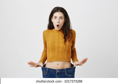 Portrait of attractive slim woman expressing astonishment and amazement, stretching jeans, showing she lost weight after signing on fitness, standing over gray background. Visible result of exercises