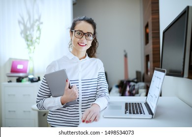 Portrait of attractive smiling businesswoman with brown curly hair, ponytail and eyeglasses dressed casual holding tablet while leaning on desk. Office interior.